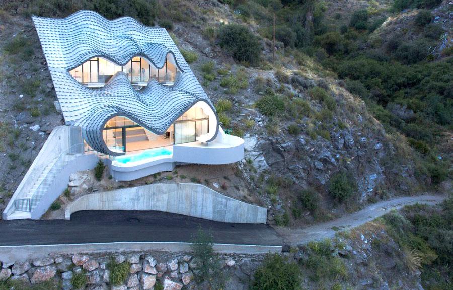 Современный дом в виде пещеры на скале
